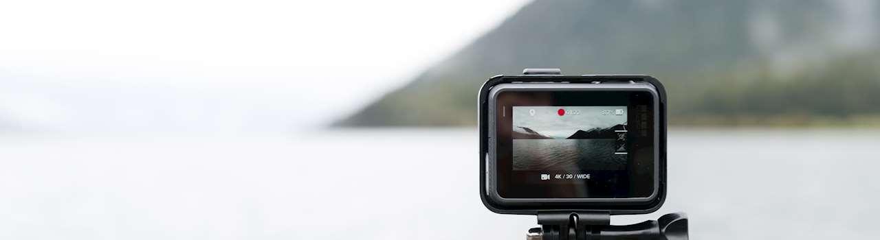 Vy över hav och berg och i förgrunden ser man motivet genom en kameras display