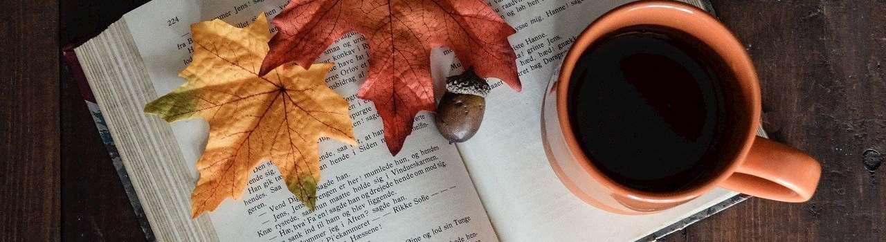 En kopp kaffe och ett par höstlöv ligger på en upplagen bok